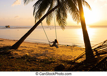 The girl on the beach rides on a swing during sunset. Sunset in the tropics, enjoying nature. Swing tied to a palm tree by the ocean