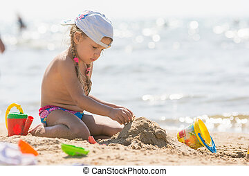 The girl on the beach seaside playing in the sand