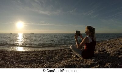 The girl on the beach sits with a tablet.