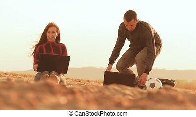 the girl on the sand sits man with a laptop slow motion video