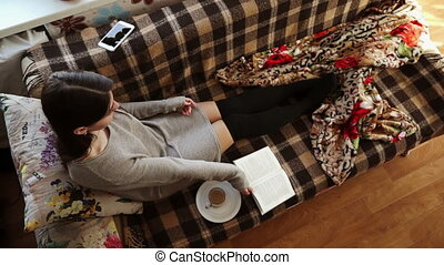 The girl on the sofa with coffee and book