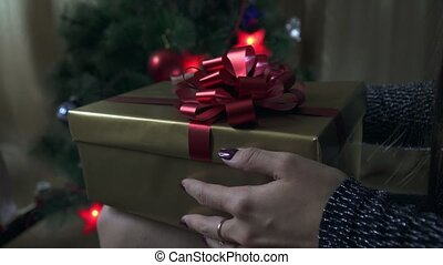 The girl opens a gift near the Christmas tree.