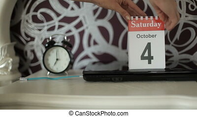 The girl opens a new calendar sheet. October 4, Saturday...