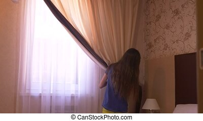 the girl opens the curtains on the window in the morning....