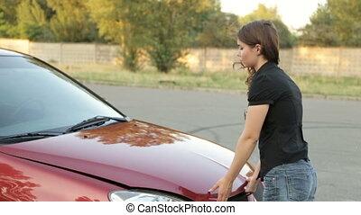 The girl opens the hood of a broken car - Girl and a broken...