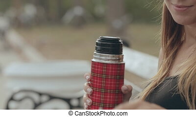 The girl opens the thermos and pours tea in the park - Girl...