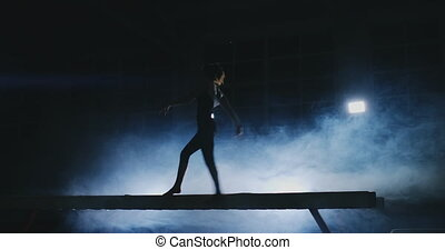 The girl performs a trick on a log in backlight and slow...