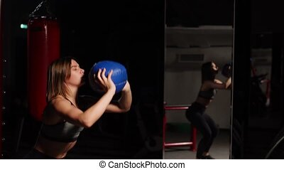 The girl performs squats with throwing the ball in her hands. Aerobic training.