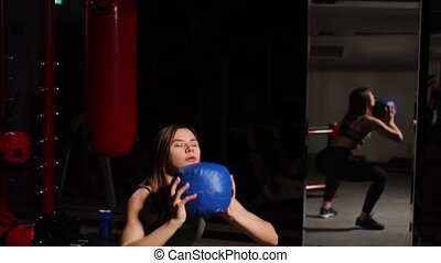 The girl performs squats with throwing the ball in her...