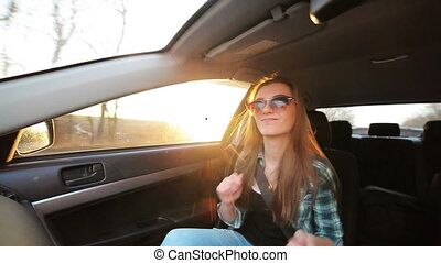 The girl photographed themselves in the car at sunset