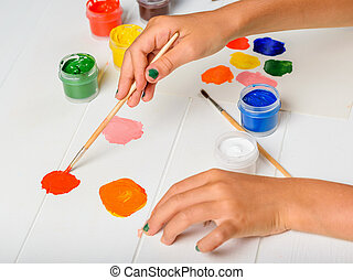 The girl picks up the red color in the palette on a white table.