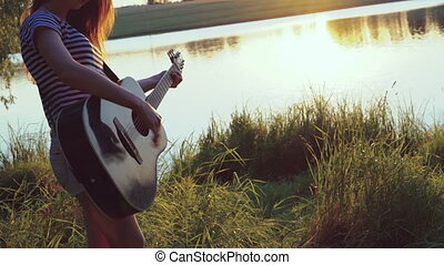 The girl playing the guitar near the evening pond. 4k