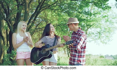 The girl plays guitar in park and friends clapping. 4k