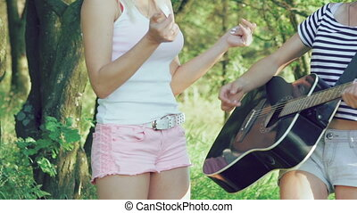 The girl plays guitar in park and friends clapping. Slowly