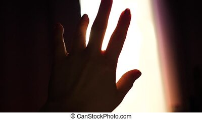 The girl plays with her hands in the sunlight. Hand close-up