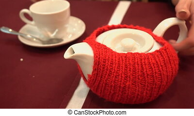 girl pours a cup of tea from the teapot on the red table