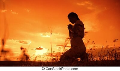 the girl prays. Girl folded her hands in prayer silhouette...