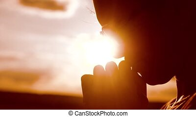 girl prays. Girl folded her hands in prayer silhouette at sunset. slow motion video. Girl folded her hands in prayer pray to lifestyle God. girl praying asks forgiveness for sins of repentance. concept Christianity religion catholicism