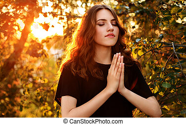 The girl prays in nature eyes closed