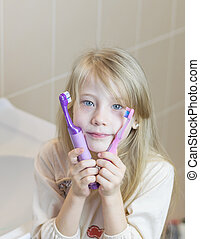 The girl presses her to face two different toothbrushes.
