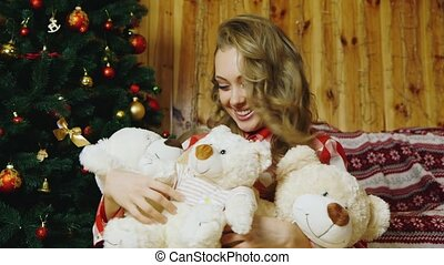 The girl presses to a lot of toy bears