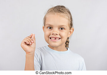 The girl proudly showing her fallen baby tooth