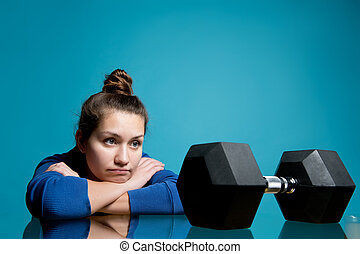 the girl put her head in her hands and looks at the dumbbell that lies in front of her