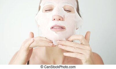 The girl puts a mask on her face. Facial skin care