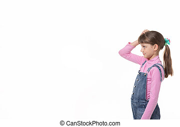 The girl puzzled scratches her head and looks at an empty spot in the frame.