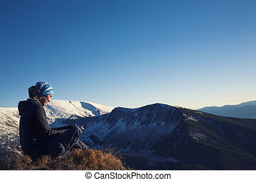 The girl relaxes in the mountains.