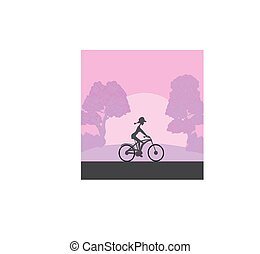 the girl rides a bicycle during sunrise