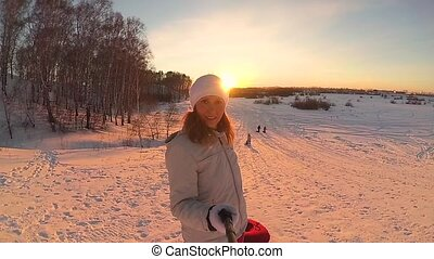 the girl rises to snowy hill with snowtube. slow motion. snow winter landscape. Active rest, sports