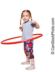 The girl rotates a gymnastic hoop