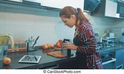 the girl rubs the carrot on the grater watching recipe on...