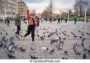 The girl run on the square and around the pigeons