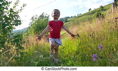 the girl runs along the path among the tall grass and wild...