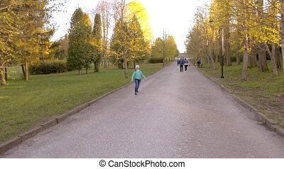 The girl  runs and dances on the path in the park