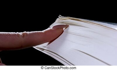 The girl runs her fingernail over the pages of a thick book, flipping through them in slow motion. Book on a black background. Close up.