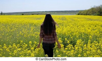 The girl runs on a field of rapeseed