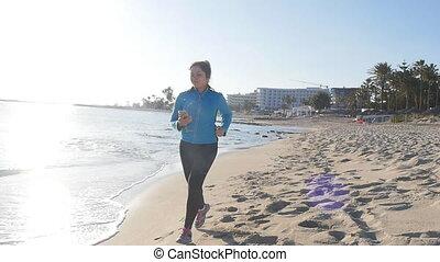 The girl runs on the beach