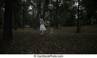 The girl runs through the park with soap bubbles