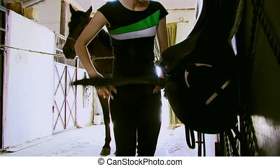 The girl saddles a horse