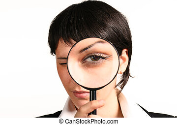 The girl searches for something through a magnifier