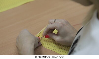 The girl sews by hand a needle and a red thread a yellow...
