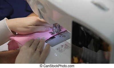 The girl sews on the sewing machine