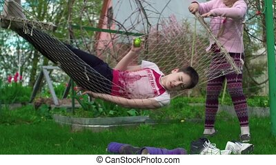 The girl shakes her hammock with a young man outdoors 4K