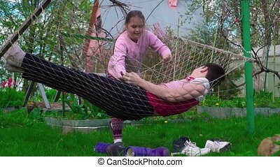 The girl shakes her hammock with a young man outdoors (slow-mo)