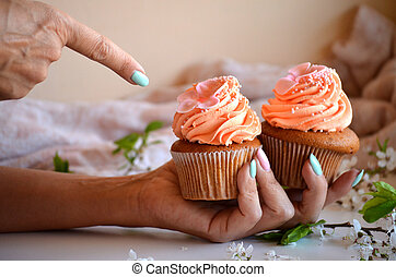 The girl shows a finger on cupcakes