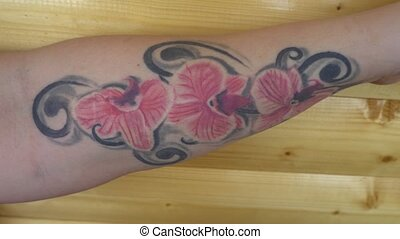 the girl shows the camera a tattoo of orchids on hand