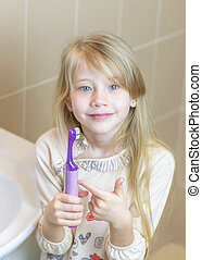 The girl shows the delights of an electric toothbrush.